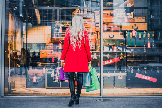 Woman looking at window shop - Young pretty girl standing in front of a boutique holding shopping paperbags