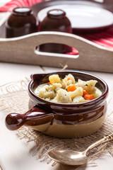 Homemade cauliflower soup in a brown bowl.