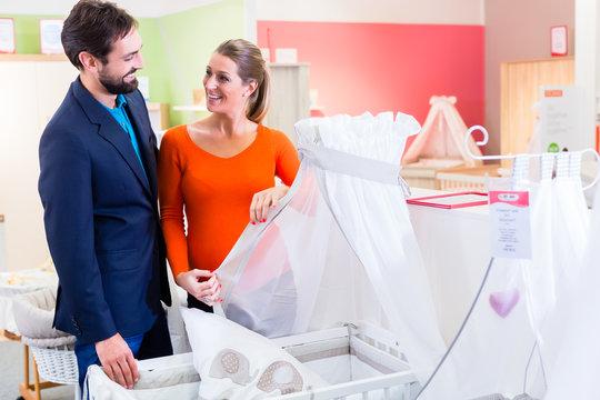 Paar erwartet Baby kauft Kinderzimmer bei Babyausstatter, Frau und Mann werden eine Familie