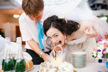Impatient beautiful bride in white dress leaned forward quickly and wants to try the wedding cake, groom wearing turquoise tie stands nearby. Celebration, cake cutting. Wedding banquet at  restaurant.