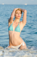 Blonde woman with amazing slim body wear bikini kneeling in the sea, waves hitting her body