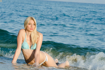 Blonde woman with amazing slim body wear bikini lying in the sea, waves hitting her body