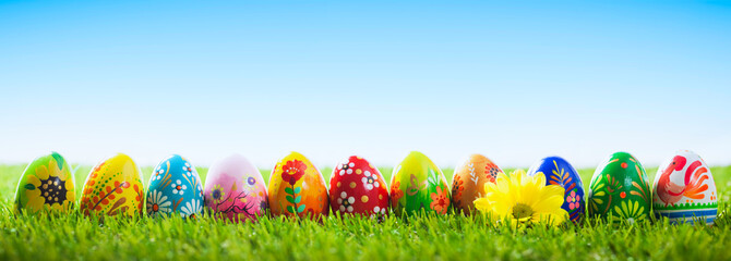 Colorful hand painted Easter eggs on grass. Banner, panoramic