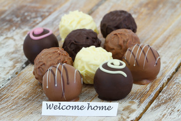 Welcome home card with assorted chocolates on rustic wooden surface