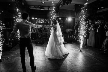 Foto op Aluminium Dance School Beautiful newlywed couple first dance at wedding reception surrounded by smoke and lights and sparks b&w