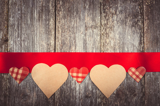 Valentines Day background - many hearts on red ribbon on wooden background. text space. Instagram color toning