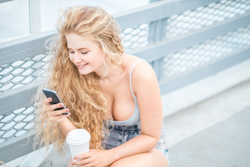 Chatting and surfing / Beautiful young woman with long curly hair and a takeaway coffee cup, chatting and surfing on the phone against urban metal railing background.