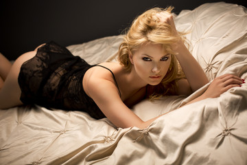 Sexy beautiful blonde woman lying in bed in sensual black lingerie, looking at camera