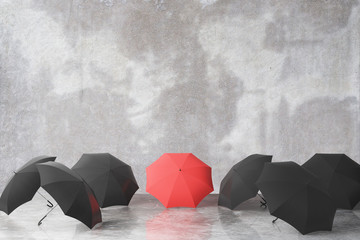 Group of black and one red umbrella