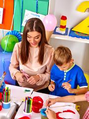 Little boy with teacher woman painting on paper  in  kindergarten .