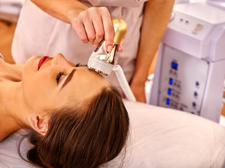 Young happy woman receiving electroporation  facial gold therapy at beauty salon.