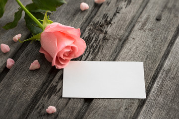 Pink rose with blank envelope and small pink decoration on woode