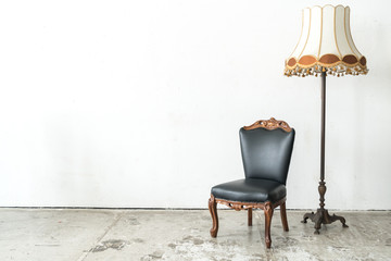 vintage armchair and lamp on white wall.