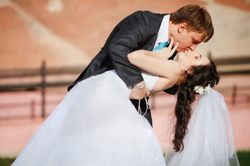 Groom gentle tilted bride, holding her in his arms and passionately kisses, wedding photo on a sunny day, background of sand-colored walls. Newly married couple dancing at park, street tango.