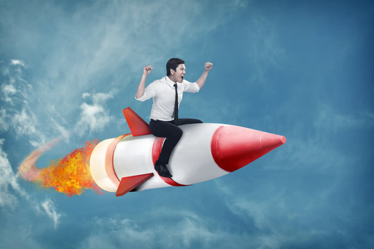 asian business man flying ride rocket