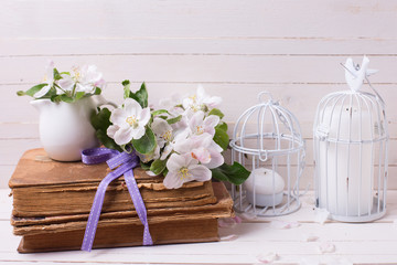 Postcard with apple blossom,  old books and candles in decorativ