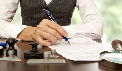 Notary signs the documents in office