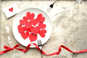 Red heart shaped paper cut out on the white dish with red heart message card