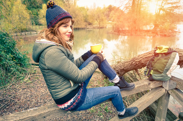 Young woman drinking coffee outdoor by the river in a landscape of wilderness - Girl on vacation enjoying the beauty of nature - Concept of travel and adventure vintage filter look with winter tones