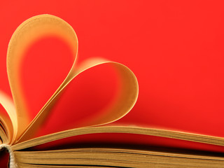 old book pages in heart shape red background