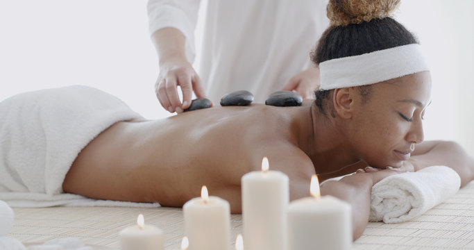Young woman getting hot stone massage in spa salon
