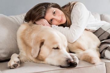 Woman laying on her dog and smiling