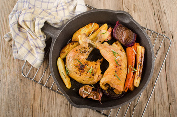 grilled chicken drumsticks with vegetable in a cast iron pan