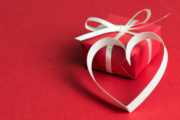 Red gift box with a heart shape symbol