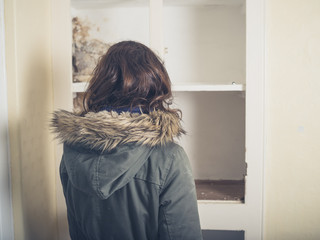 Woman in coat looking at old cupboard