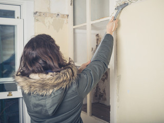 Woman in coast stripping wallpaper