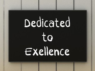 dedicated to excellence on black board. Business concept.
