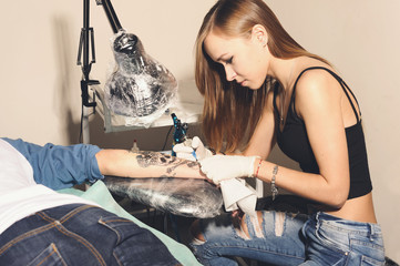 Young beautiful woman tattooer showing process of making a tattoo black skull with crown design.