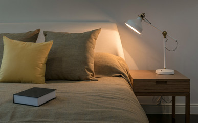 Cozy bedroom interior with book and reading lamp on bedside table