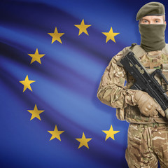 Soldier with machine gun and flag on background - European Union - EU
