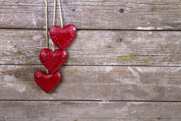 Valentine's day ornament on wood background. wooden two red hearts on old wooden gray background
