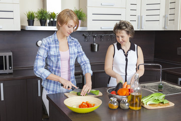 Mother and adult daughter preparing a salad in the kitchen