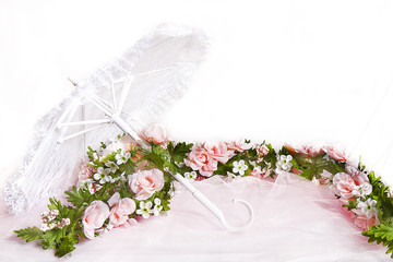 White lace parasol with pink tulle fabric intertwined with soft pink roses in a garland.  Background
