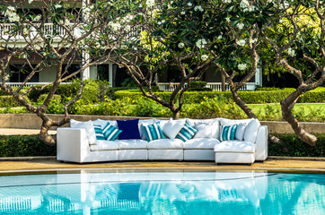 Outdoor sofa with cushions and pillows in the garden by the pool