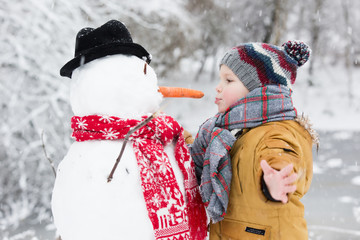 boy playing with a snowman