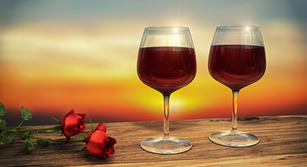 Two wine glasses filled with red wine with two red roses during sunset