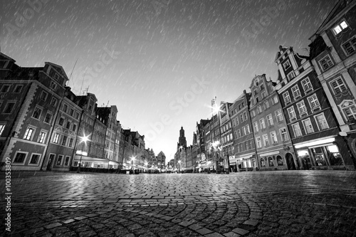 Fototapete Cobblestone historic old town in rain at night. Wroclaw, Poland. Black and white