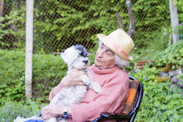 beautiful Senior smiling woman with straw hat hugging her small white poodle dog in the mountain