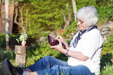 beautiful senior woman with white hair sitting in the garden counting the money in her wallet