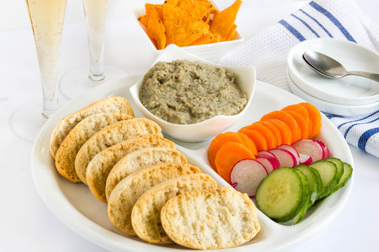 Party appetizers with lentil puree, vegetables, toast and tortilla chips.