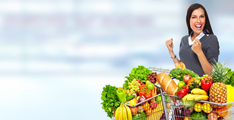 Fototapete - Happy young woman with grocery shopping cart.