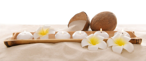 Coconut with candles and plumeria on sand, isolated on white