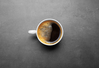 Cup of coffee on grey background, top view