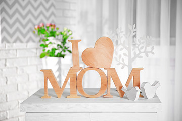 I love mom inscription of wooden letters with heart on a white table