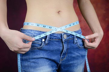 slim woman measuring body, wearing jeans