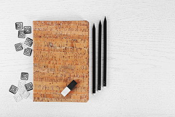 Notebooks with clips, eraser and pencils on a white table
